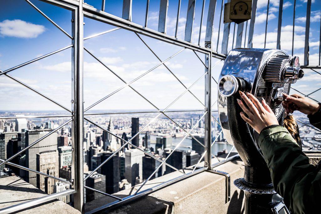 Blisko dziewczyny, która wygląda na Manhattan teleskopem, z Empire State Building