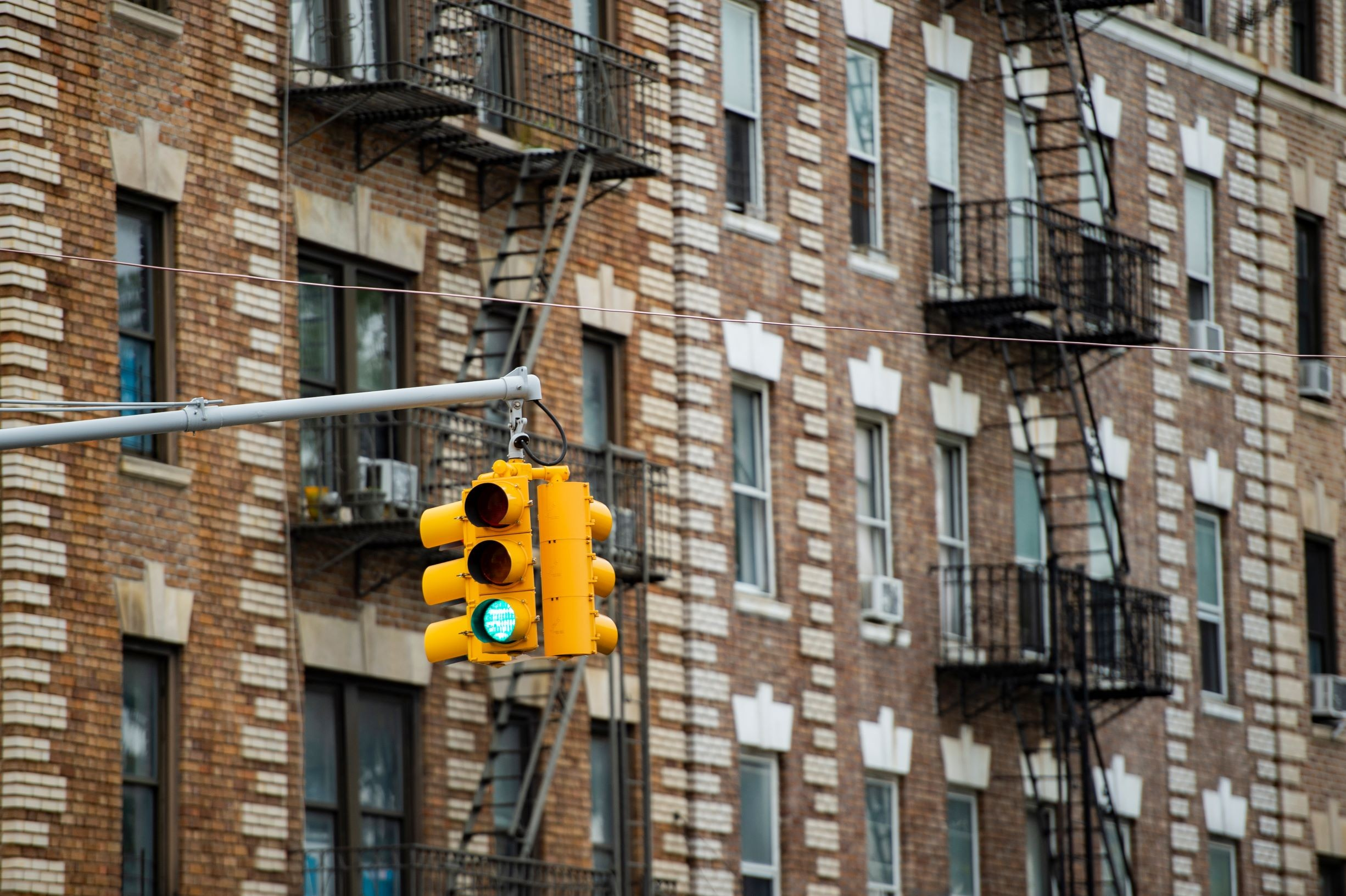 Close-up view of a traffic light and some buildings on background with windows and emergency stairs. Bronx District, New York, USA.