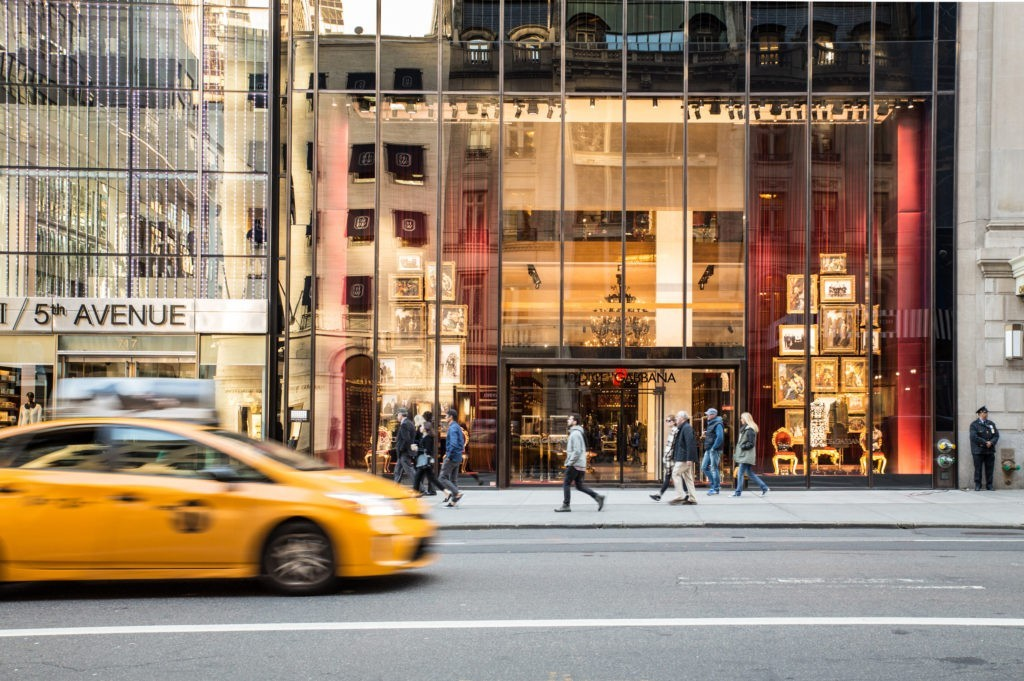 NEW YORK CITY - OCTOBER 15, 2015:  Midtown Manhattan street view along the upscale shopping district on 5th Avenue with cars and people.