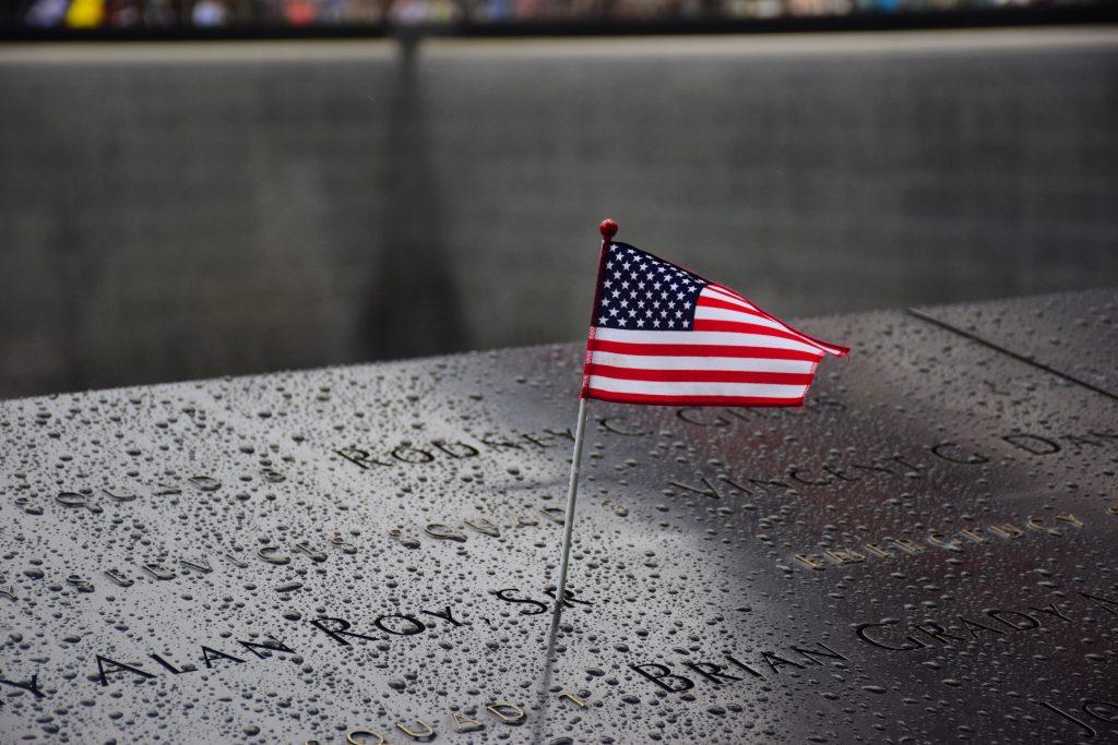 Pomnik na Ground Zero Manhattan za atak terrorystyczny 11 września z amerykańską flagą stojącą w pobliżu Imion ofiar wygrawerowane