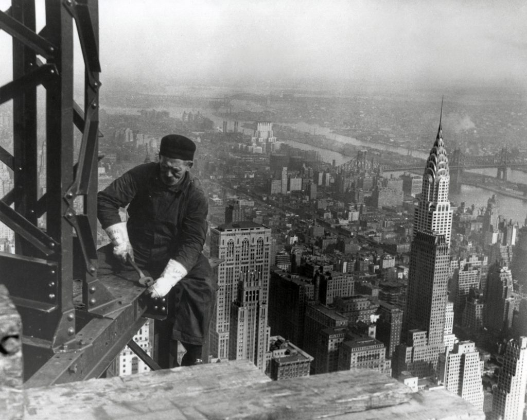 W średnim wieku robotnik żelaza na budowie Empire State Building, 1930. Iglica budynku Chryslera jest w prawo. Zdjęcie Lewis Hine.
