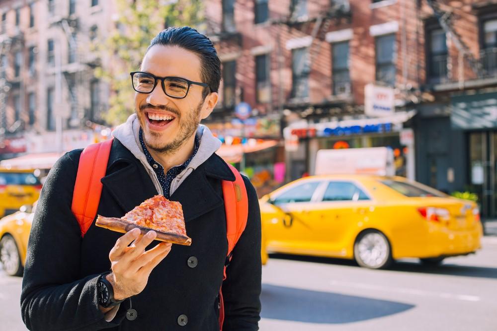 Człowiek zjada kawałek pizzy w Nowym Jorku