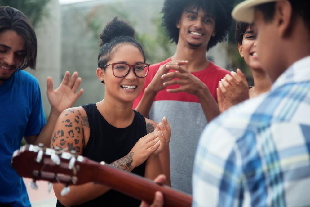 Młodzi ludzie słuchający koncertu gitarzysty