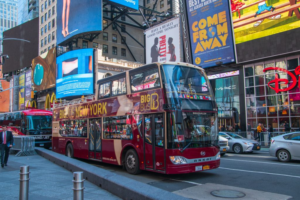 New York, NY - April 3, 2019: Double decker hop on / hop off tour bus seen on broadway in Times Square Manhattan New York City